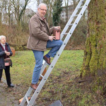 Erich Schulz hängt einen Meisenkasten an einen Baum